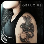 Skull Holding Gryphon Shoulder tattoo by BRÜCIUS