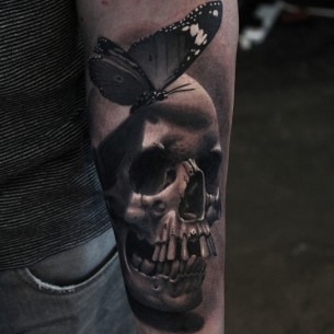 Realistic Butterfly on Skull Arm tattoo