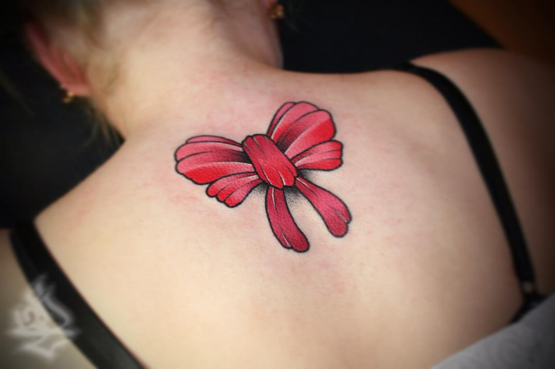 red bow tattoo on back