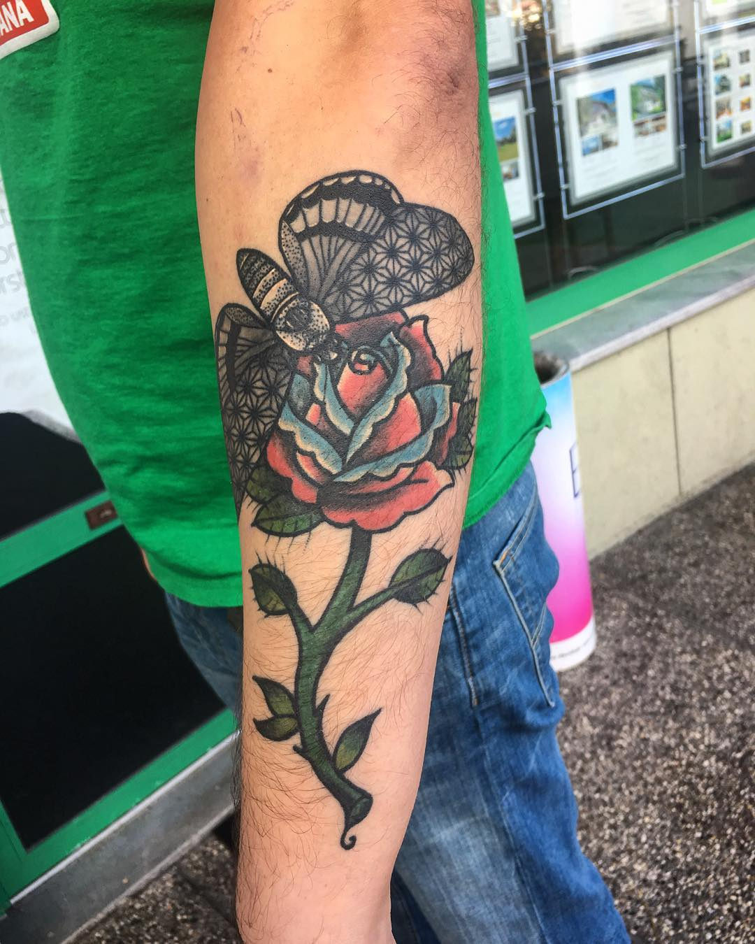 a classical tattoo plot - a butterfly sitting on the rose