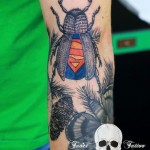 A tattoo of a bug with a superman mark on its back