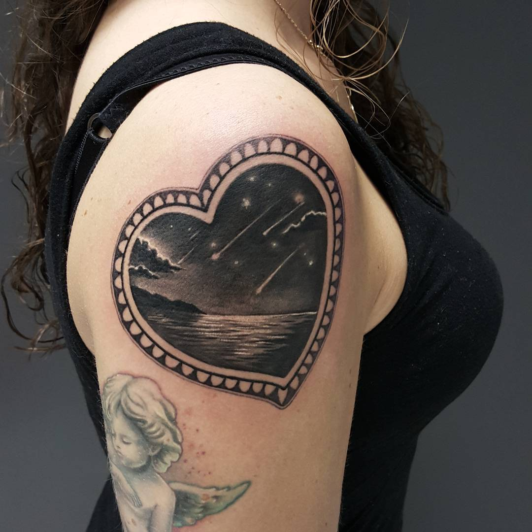 heart shaped frame and seashore and falling stars inside it. Tattoo on shoulder