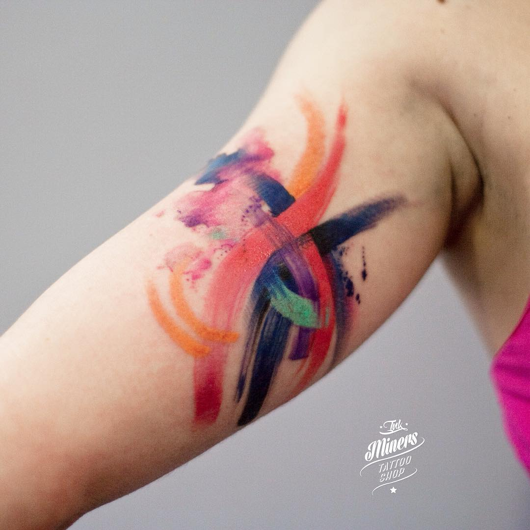 colorful brushstrokes on bicep tattoo