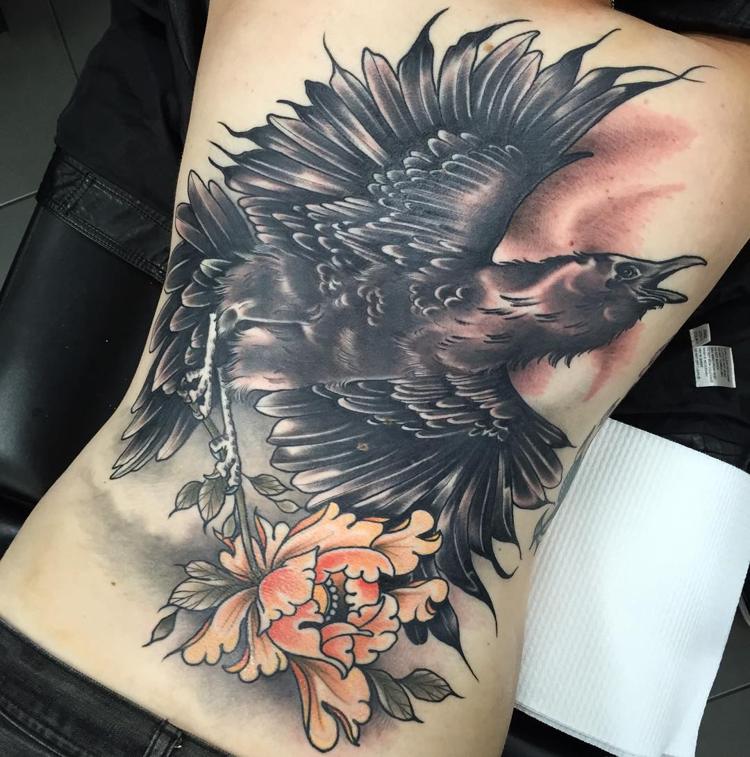 huge crow tattoo on full back with a flower in its claws