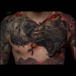 a big chest tattoo of two angry dogs