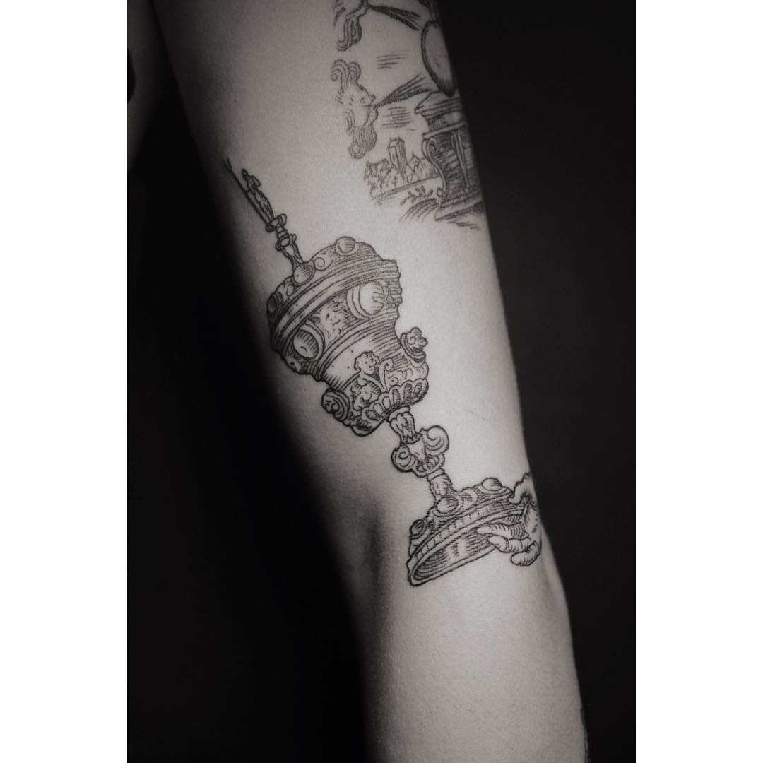some luxury cup is depicted in this arm tattoo