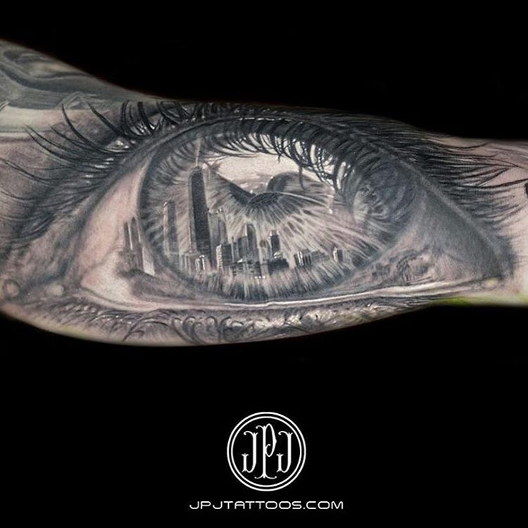 very realistic black and grey tattoo of an eyeball with a detailed reflection of a big city on the picep