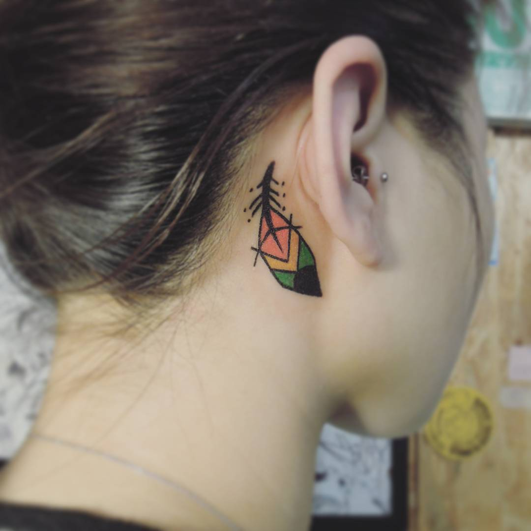 small colorful feather tattoo which looks like something Indian placed behind girl's ear