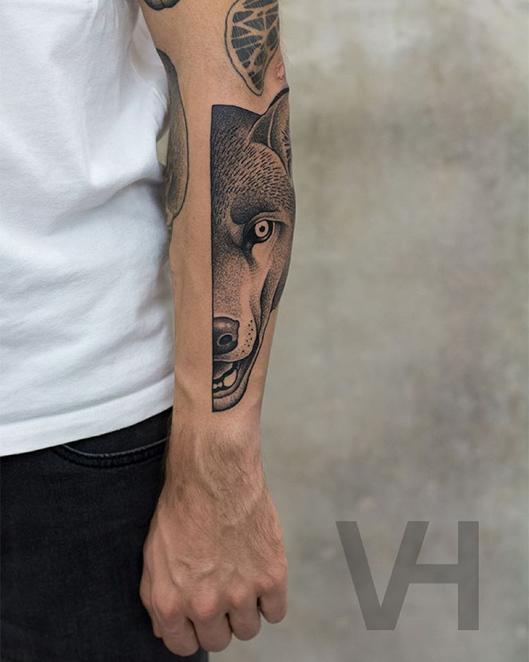 a tattoo on arm of the half of the wolf's face