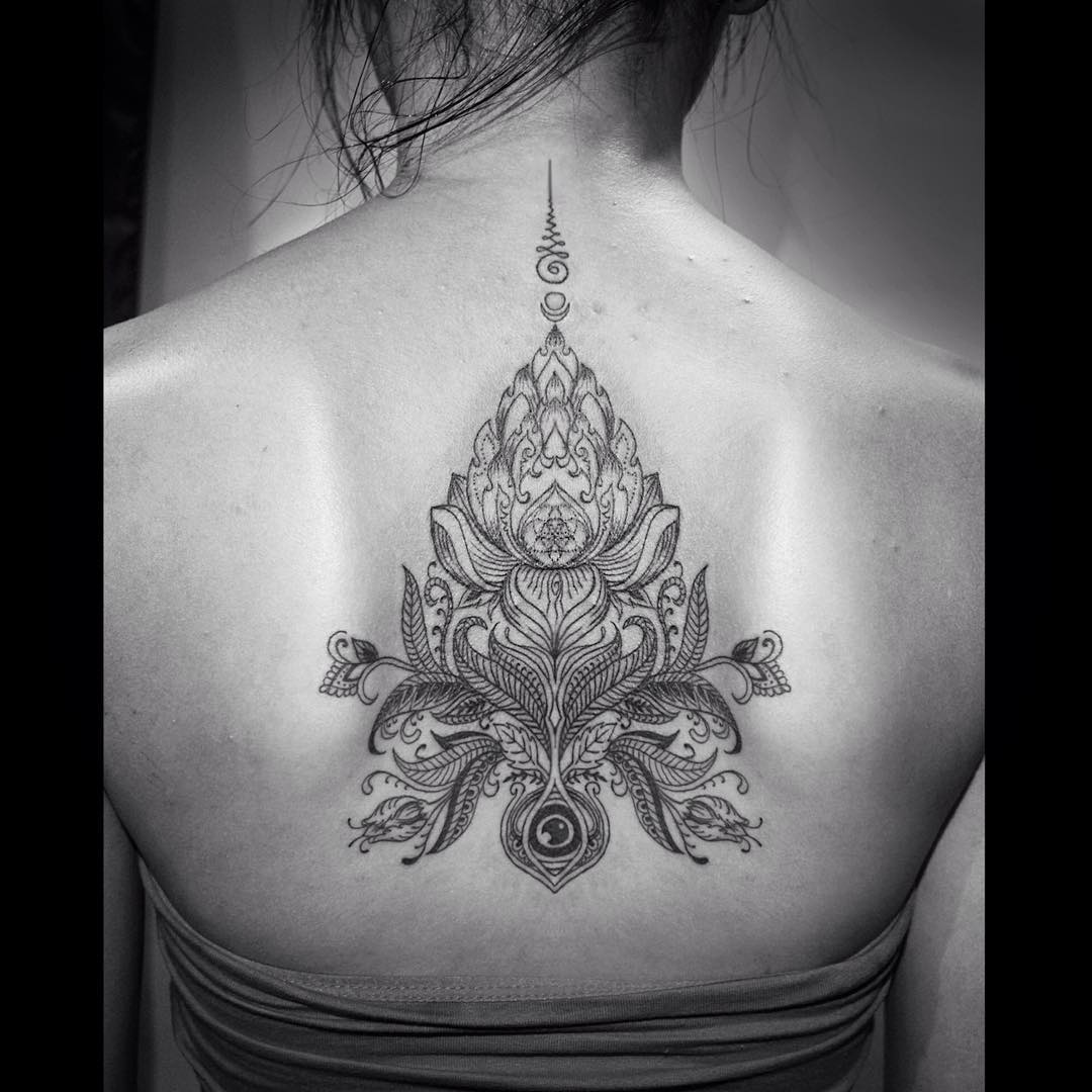 detailed religious drawing of the lotus flower between shoulder blade