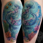 tattoo of two mermaids swimming in the blue ocean