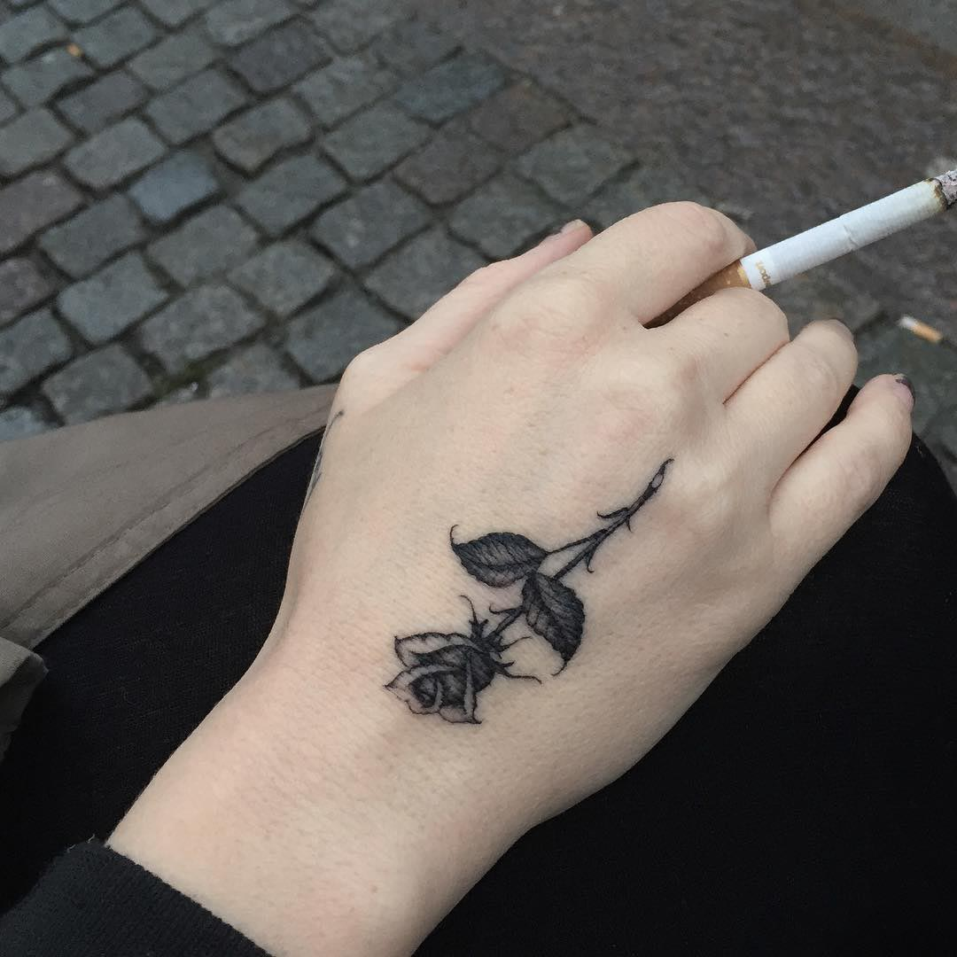 a small black rose tattoo on hand