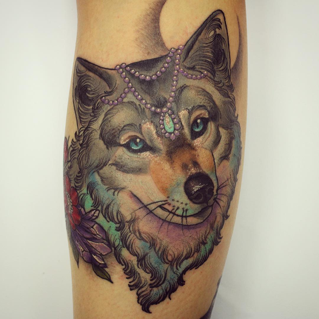 The tattoo of a lovely wolf head with some accessories on it