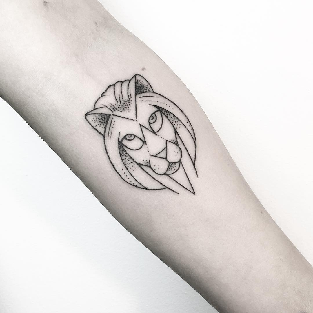 small stylized face of a lion on a forearm
