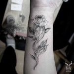 snake and rose tattoo on inner arm