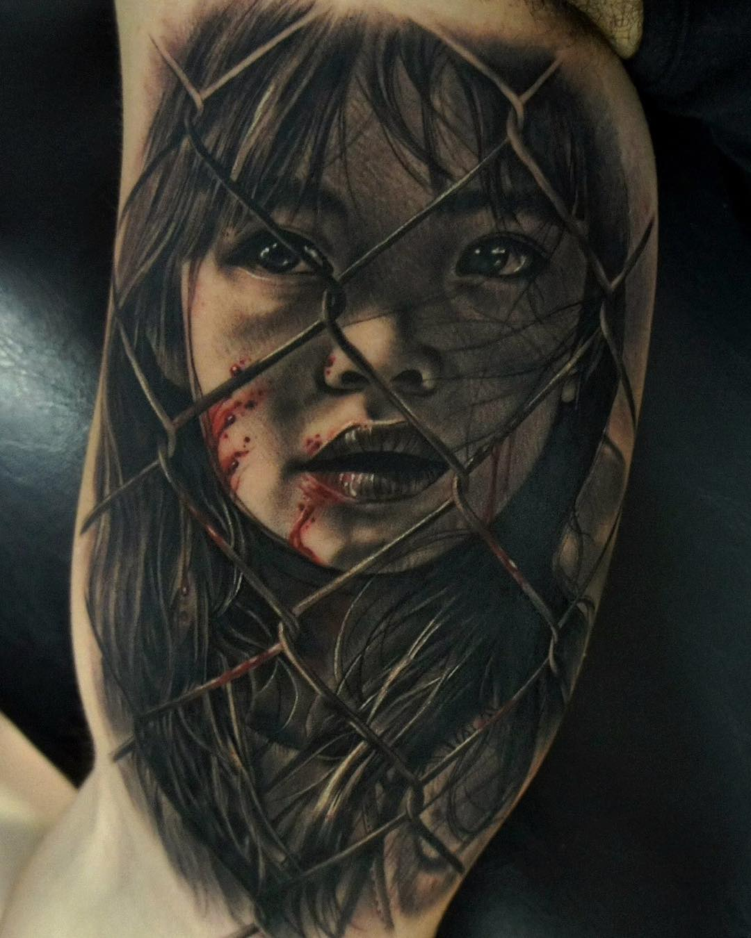 the black and grey portrait of a girl behind the fence - realistic tattoo