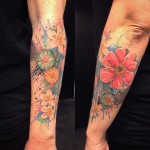 forearm decorated with many little flowers in watercolor tattoo style