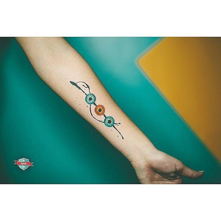 three eyeballs tattoo on arm