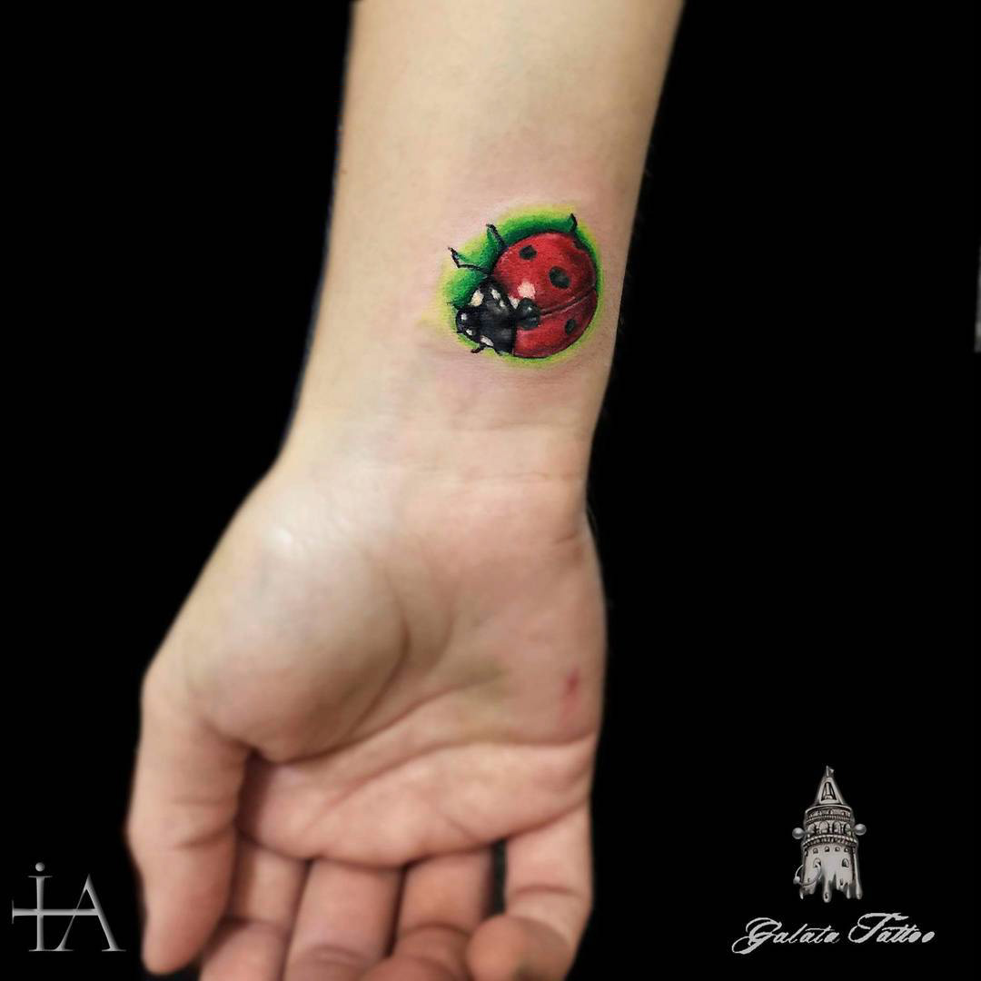 small ladybug tattoo on wrist