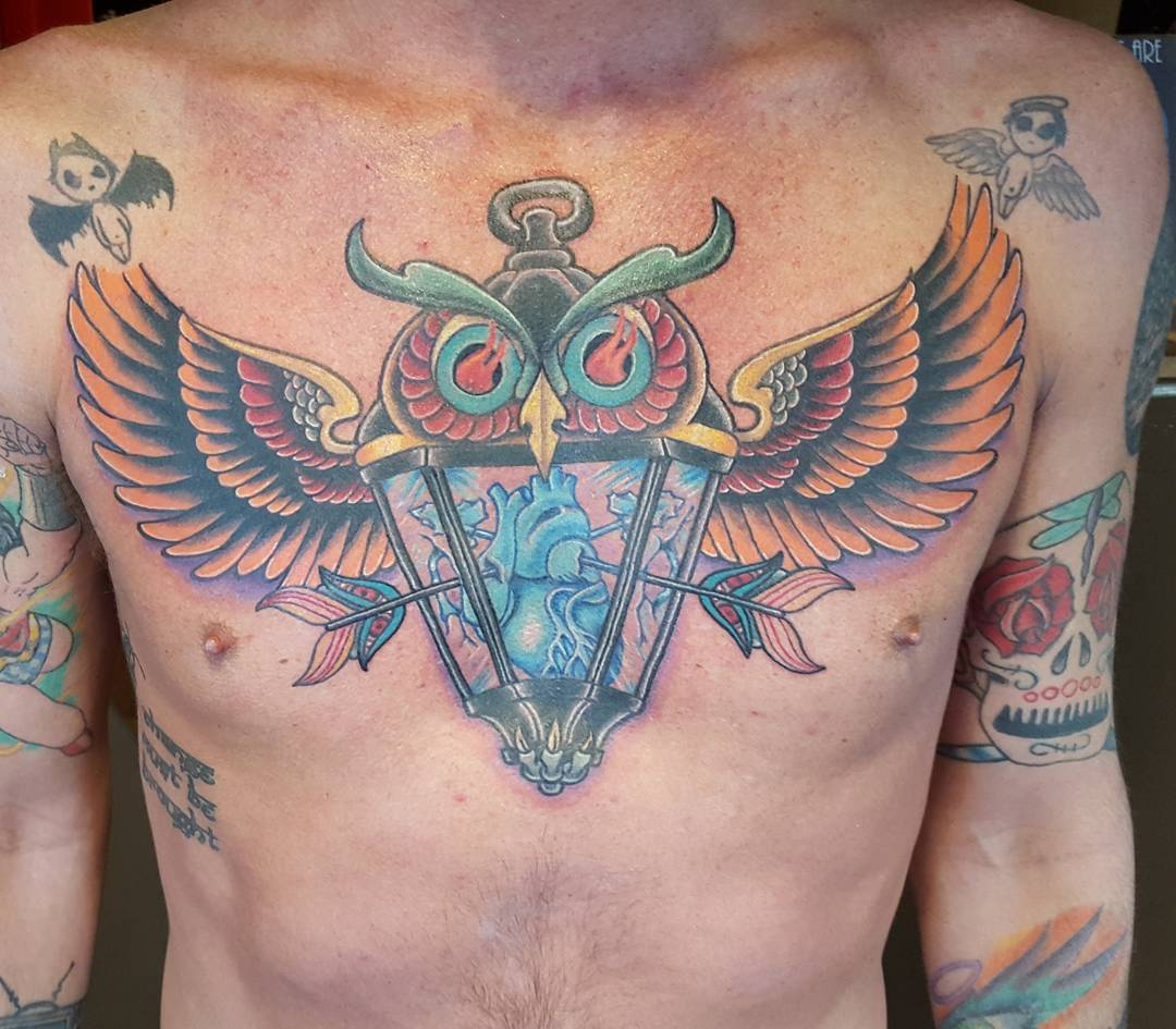 owl and lantern tattoo on chest