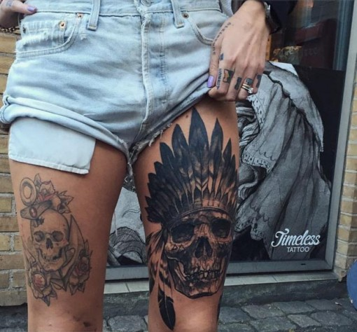 skull feathers tattoo on thigh
