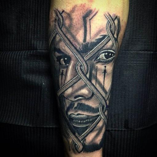 Chicano tattoo man behind fense