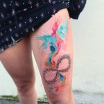 bright watercolor tattoo on thigh