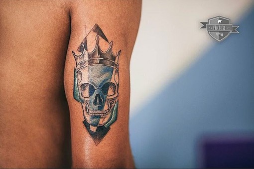 skull with crown tattoo on arm