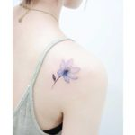 flower bluish tattoo on back of shoulder