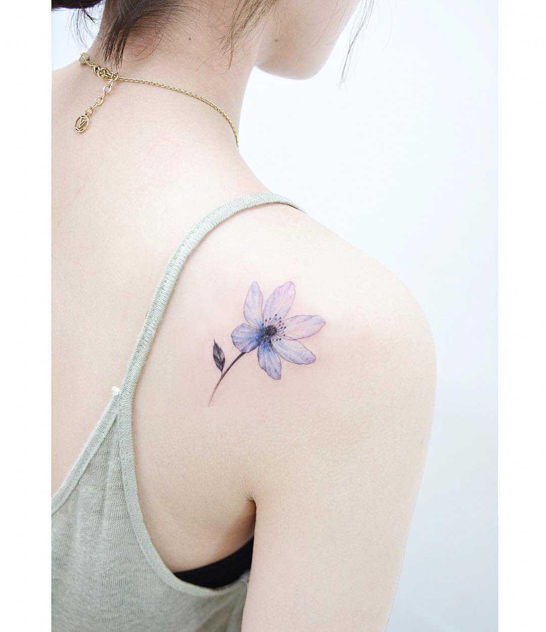 flower bluish tattoo on back of shoulder