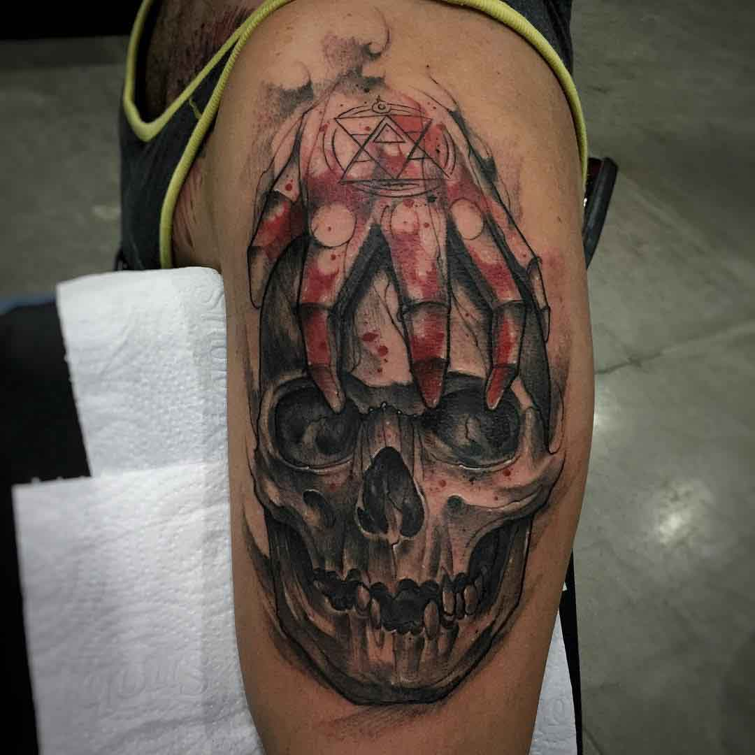 skull with hand tattoo on shoulder