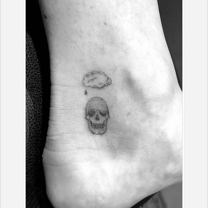 cloud skull small tattoo on heel side