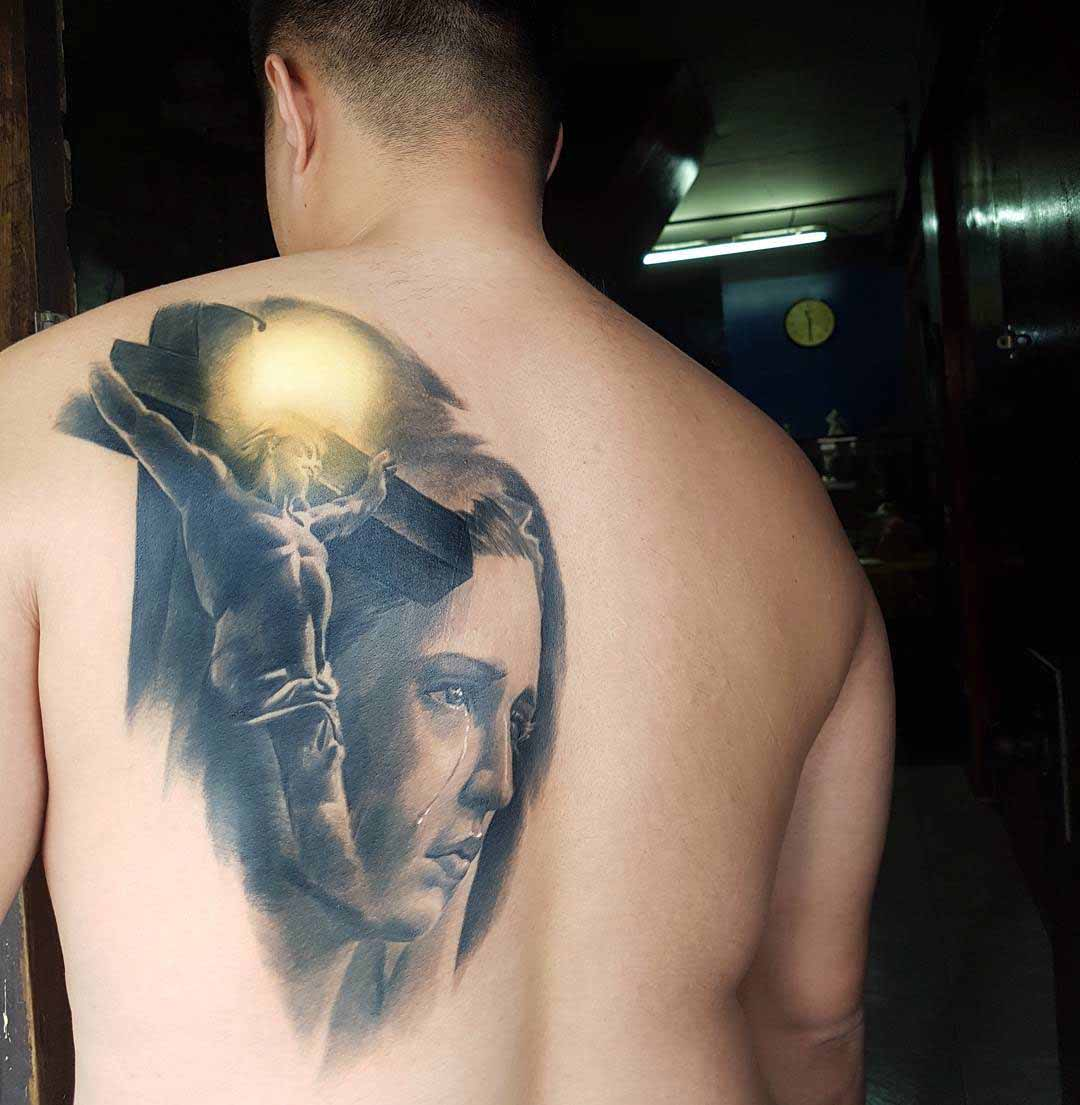 back religious tattoo on shoulder blade crying Mary and Jesis