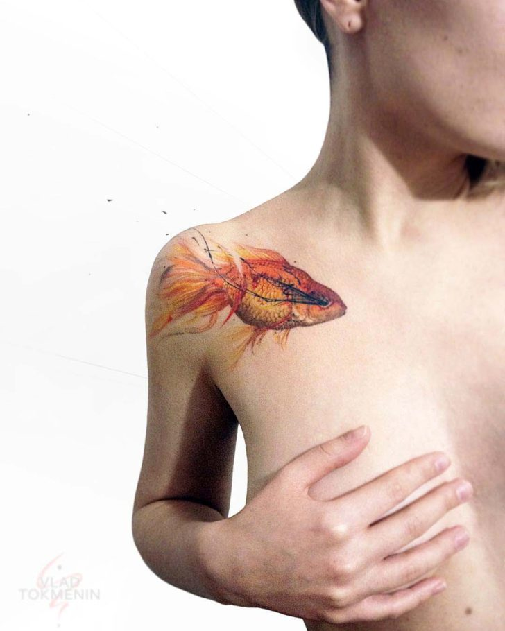 gold fish tattoo on collar bone