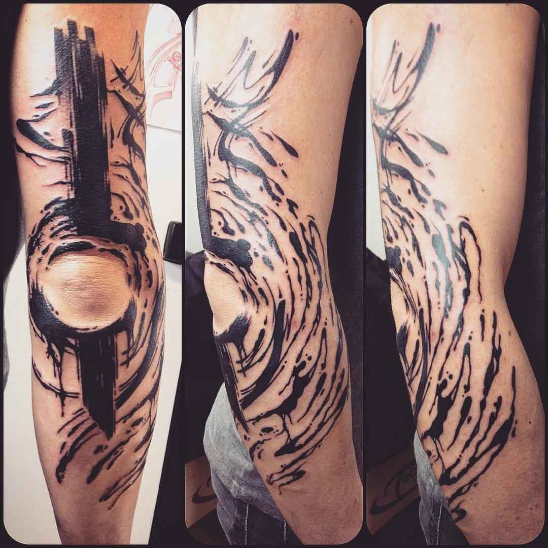 black brush strokes tattoo around elbow