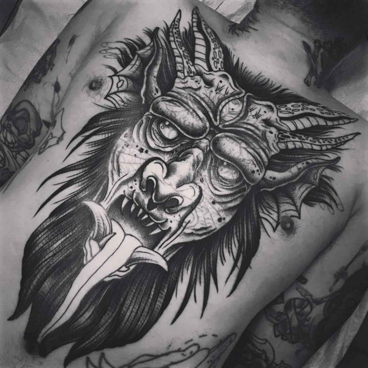 demon face tattoo on chest and stomach
