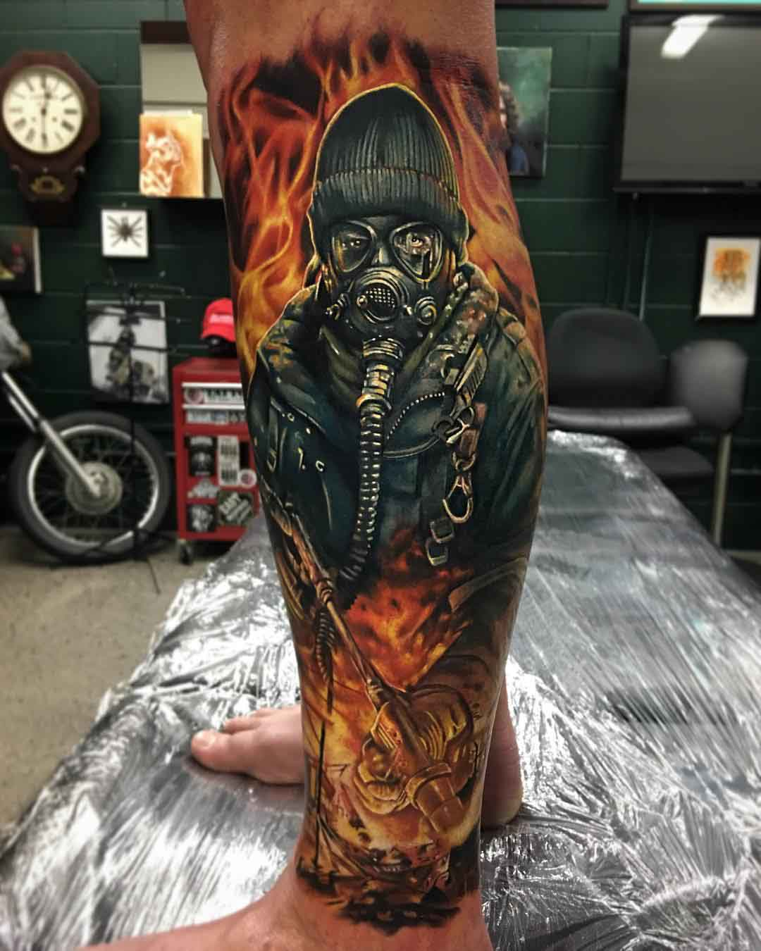 leg tattoo flaming man in gas mask