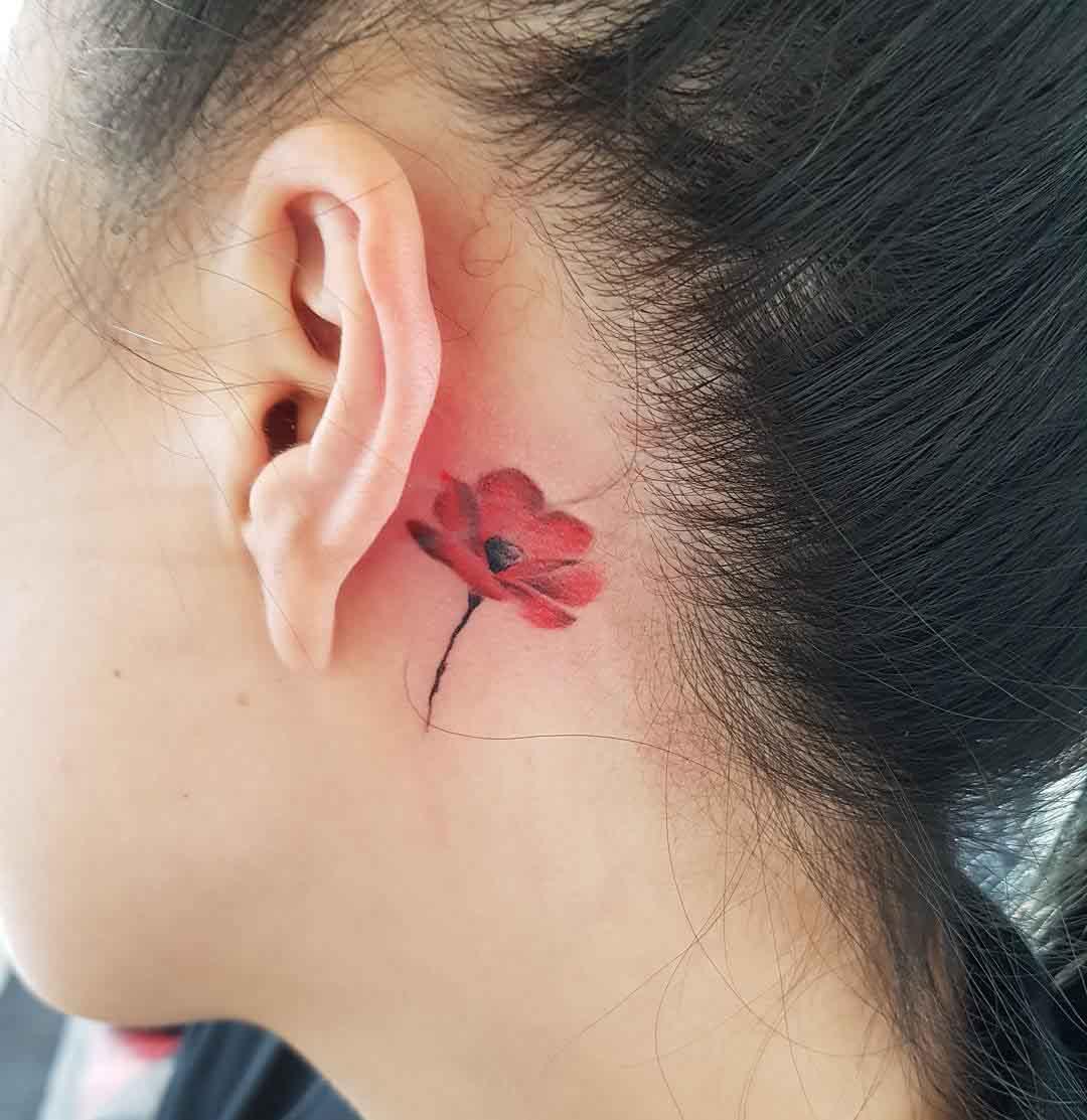 little poppy tattoo behind the ear