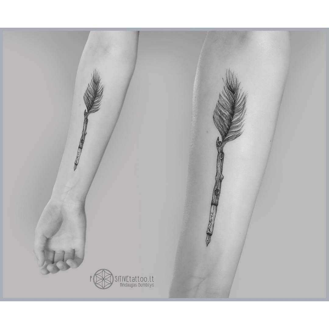arm tattoo feather pen