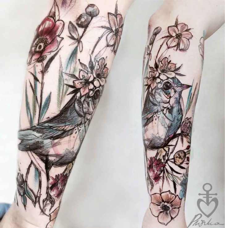 bird in flowers tattoo on forearm