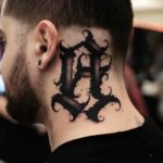 Dark Lettering Tattoo on Back of Neck